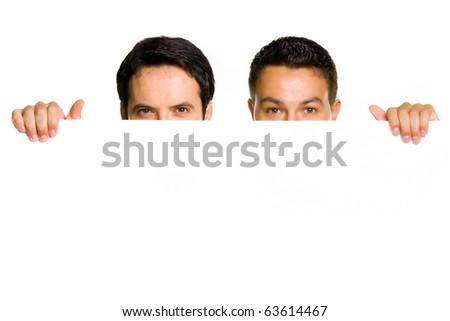 Two young guys holding a blank billboard, studio shot - stock photo