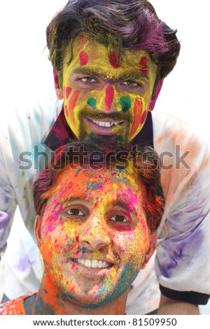 Two young guys with their faces tradiitionally painted in colorful powders, on the occasion of holi festival in India. - stock photo