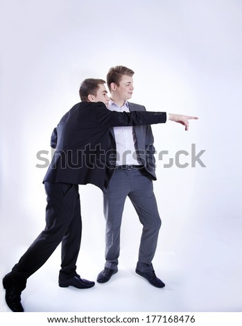 Two young handsome businessman talking, showing something. Studio shot. Conceptual photo. - stock photo