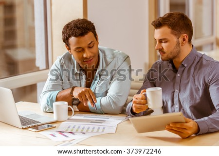Two young handsome businessmen in casual clothes talking, drinking coffee, using laptop and tablet while working in office - stock photo