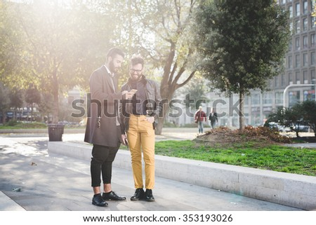 Two young handsome caucasian bearded brown hair businessmen standing in the city, backlight, both looking downward and tapping the screen of smartphone handhold - business, technology, work concept