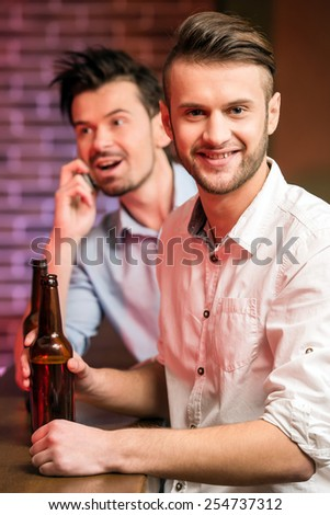 Two young handsome friends in a pub with bottle of beer are spending time together. - stock photo