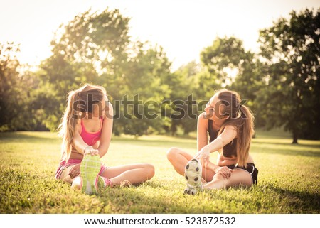 Two young happy caucasian woman friends stretching at the park after a running workout
