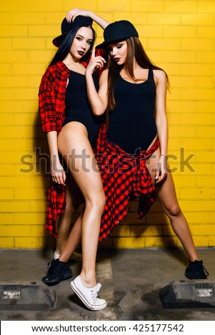 Two young happy hipster girls having fun, smiling, laughing, jumping, walking  near urban yellow wall background, summer relax concept
