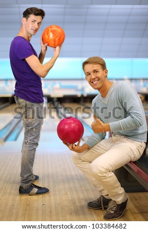 Two young happy men hold balls in bowling club; right man sits and thumb up; left man prepares to throw ball and looks at camera; focus on right man; shallow depth of field - stock photo