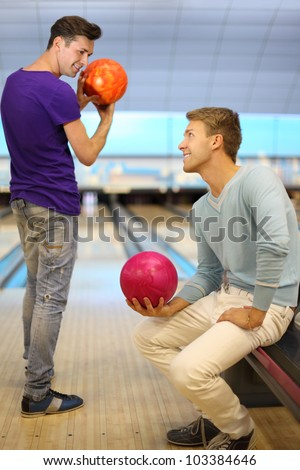 Two young happy men hold balls in bowling club; right man sits; left man prepares to throw ball; focus on right man; shallow depth of field - stock photo