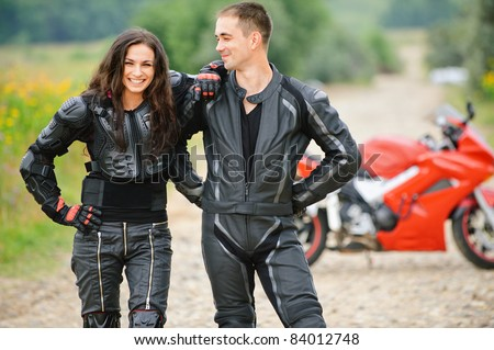 Two young happy people wearing leather costumes against red motorbike. - stock photo