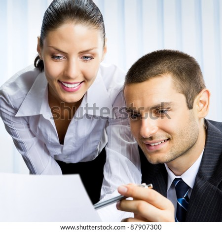 Two young happy smiling successful businesspeople working with document or contract at office - stock photo