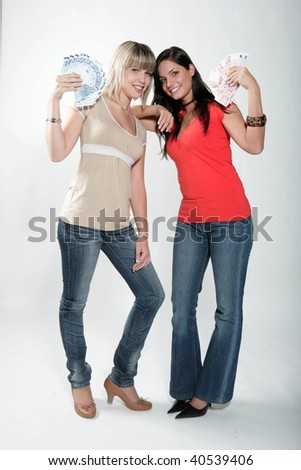 Two young happy women holding money - stock photo