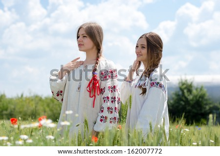 Two young happy women in traditional ukrainian dress in wheat field on summer day - stock photo