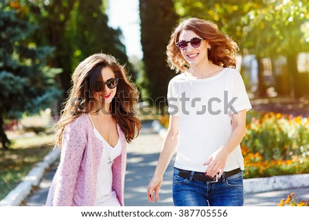 Two young happy women walking in the summer city - stock photo