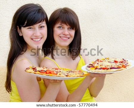 Two young happy women with pizza
