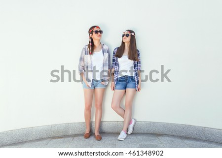 Two young hippie girls are standing in front of the white curved wall and looking away. They wear matching outfits, plaid shirts and denim shorts, sunglasses and flowers hair accessories.