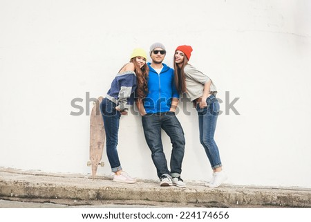Two young hipster girl friends and guy together having fun. Outdoors, lifestyle. - stock photo