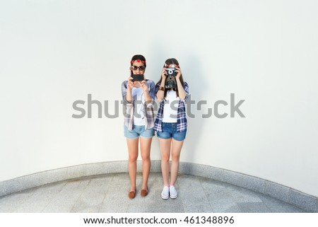 Two young hipster women are taking photos. One of them is using smart phone and the other is using vintage camera. Girls are wearing matching outfits, plaid shirts and denim shorts