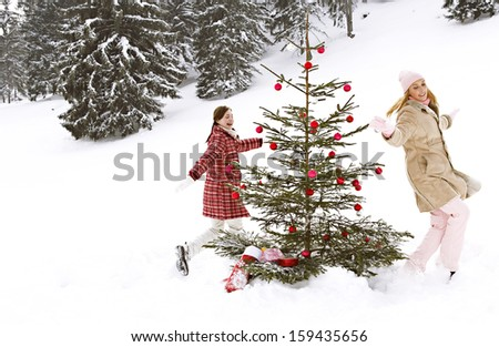 Two young joyful and attractive girls friends playing, chasing and running around a decorated christmas tree in the snow mountains nature, celebrating xmas and having fun together. - stock photo