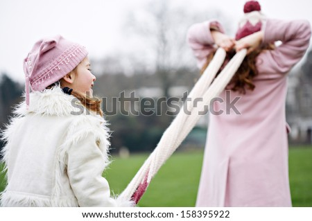Two young joyful sisters family children playing together and having fun with games, pulling a woolly scarf in a green park field during a cold winter day, outdoors. - stock photo