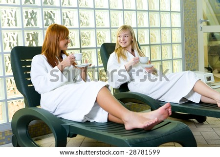Two young ladies clothed bathrobe sitting on deckchairs. They're talking and drinking coffee. - stock photo