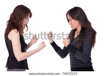 Two young ladies, facing each other with fists clenched, appearing to be in a fight - stock photo