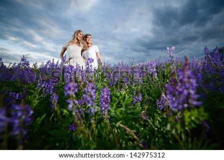 Two young ladies in a lavender field - wide-angle shot - stock photo