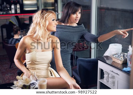 Two young ladies in a restaurant - stock photo