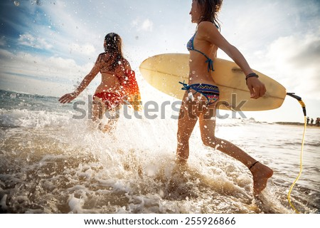 Two young ladies surfers running into sea with surf boards - stock photo
