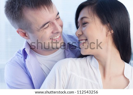 Two young lovers looking at each other and laughing