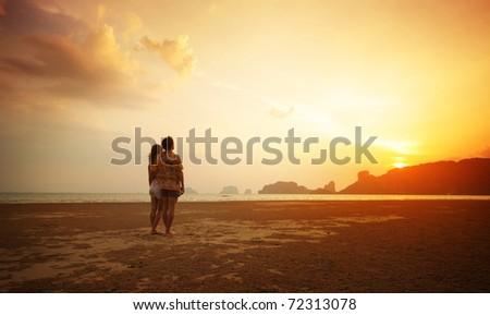 Two young lovers standing on beach and looking to a sun - stock photo