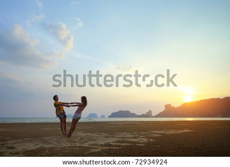 Two young lovers standing on beach and looking to each other on sunset background
