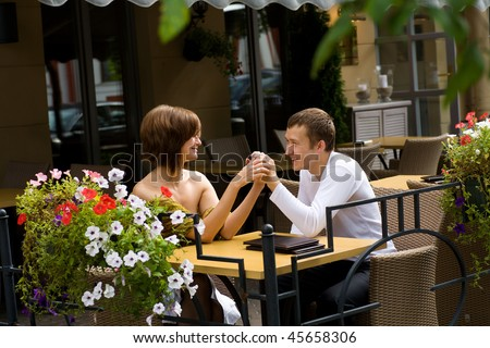 Two young lovers talking at the table - stock photo