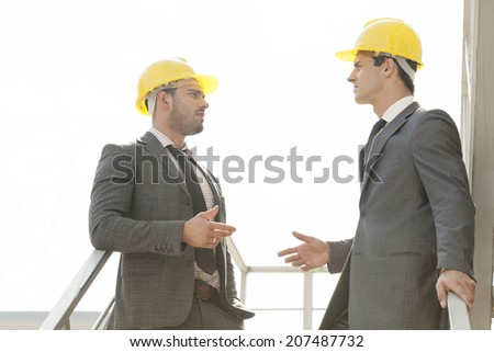 Two young male architect discussing on stairway - stock photo