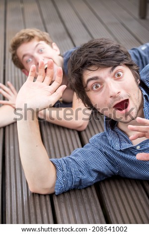Two young male models are having a lot of fun. The front model is very surprised while the one behind is doing a funny gesture - stock photo