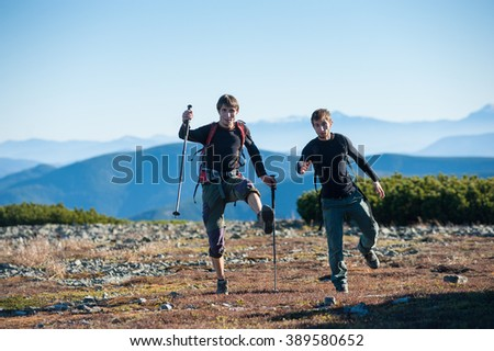 Two young male tourists having fun at the top of the mountain, high altitude meadow on warm sunny day. Healthy lifestyle concept. - stock photo