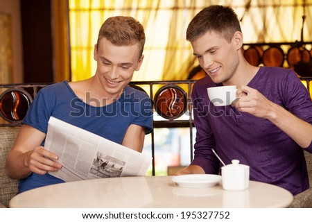 two young man reading newspaper. handsome guys drinking coffee and talking - stock photo