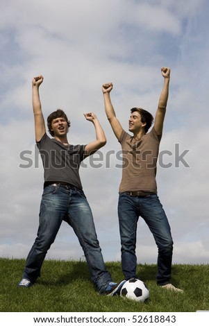 Two young man with a soccer ball celebrate - stock photo