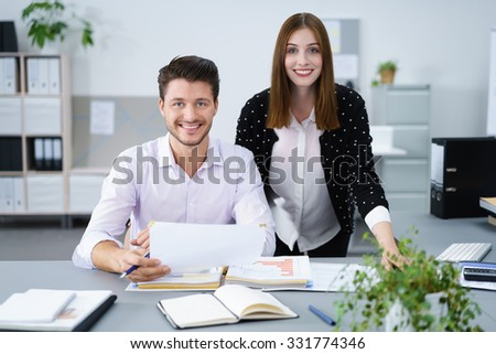 two young manager at the office smiling at camera - stock photo