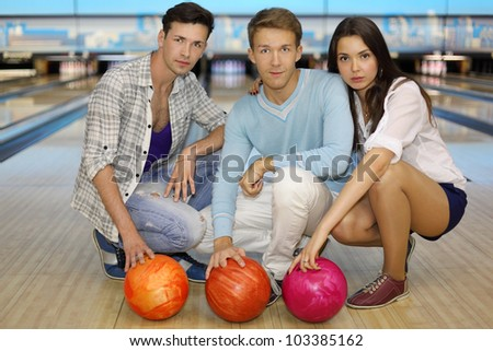 Two young men and girl sit on floor with balls in bowling club; focus on center man; shallow depth of field - stock photo