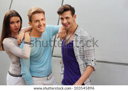 Two young men and woman stand near gray wall; focus on center man - stock photo