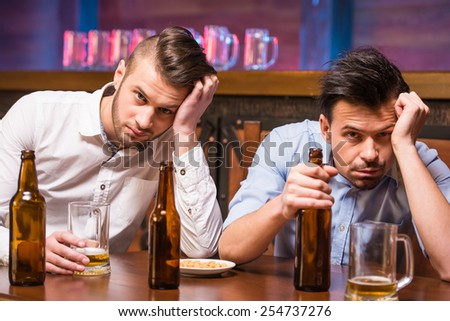 Two young men are sitting in pub with empty bottles of beer. - stock photo