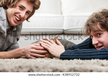 Two young men caressing a little chihuahua dog together as they all three lie on a rug on the floor , close up of the dog and their smiling happy faces - stock photo