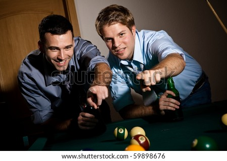Two young men discussing snooker game, having beer, pointing at table.? - stock photo