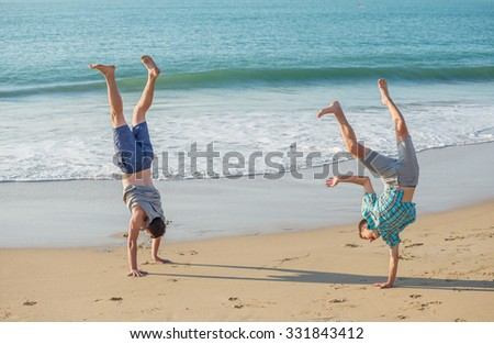 Two young men have fun on the beach  in the evening light.