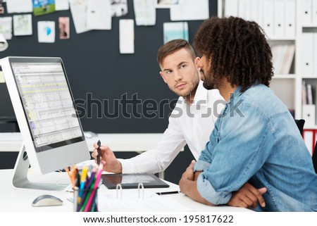 Two young men having a business meeting with an African American sitting looking at information on the computer watched closely by his colleague - stock photo