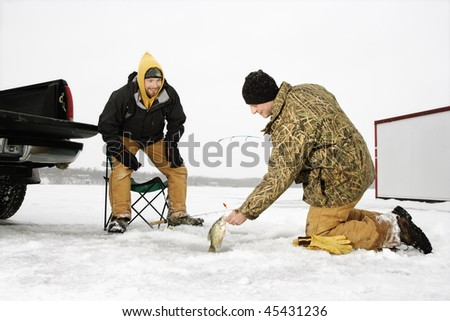 Two young men ice fishing in a winter environment. Horizontal shot. - stock photo