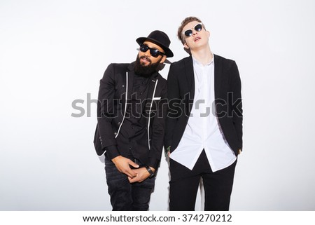 Two young men in fashion cloth standing isolated on a white background - stock photo