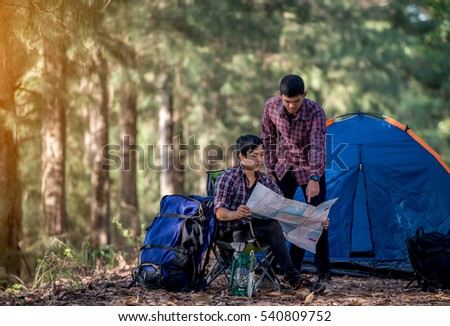 Two young men looking Travel map Inside a tent camp in the woods.