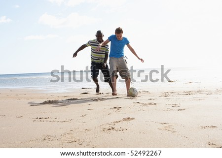 Two Young Men Palying Football On Beach Together