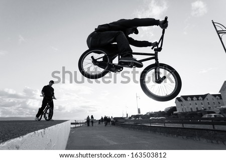 Two Young men performs BMX stunts during sunset at the street. Monochromatic - stock photo