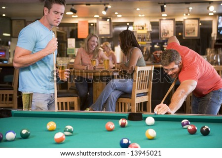 Two young men playing pool at a bar - stock photo