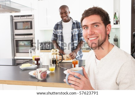 Two Young Men Preparing Breakfast In Modern Kitchen - stock photo